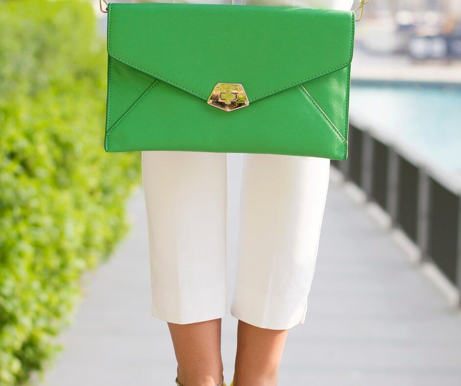 woman-in-white-trousers-and-yellow-shoes-holding-green-handbag-picture-id835804912